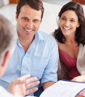 Happy middle aged couple meeting with financial advisor